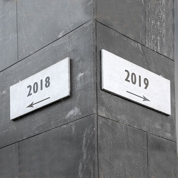 Street signs one stating 2018 and pointing left, the other stating 2019 and pointing right